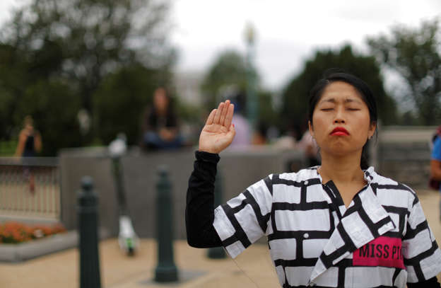 Slide 4 of 72: A demonstrator stands in silent protest with her hand up outside the U.S. Capitol as the U.S. Senate votes to confirm the Supreme Court nomination of Judge Brett Kavanaugh at the U.S. Capitol in Washington, U.S., October 6, 2018.  REUTERS/Jonathan Ernst