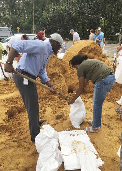Slide 47 of 47: Tallahassee Mayor and Democratic gubernatorial candidate, Andrew Gillum, left, helps Eboni Sipling fill up sandbags in Tallahassee, Fla., Monday, Oct. 8, 2018.