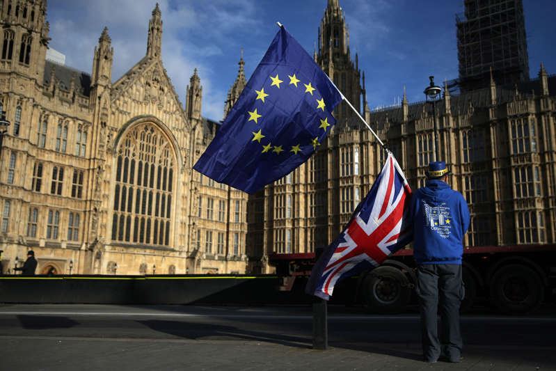 TOPSHOT - A pro-European Union,(EU), anti-Brexit demonstrator holds the EU and UK flags outside the Houses of Parliament, in central London on January 22, 2018. / AFP PHOTO / Daniel LEAL-OLIVAS        (Photo credit should read DANIEL LEAL-OLIVAS/AFP/Getty Images)