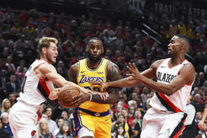 PORTLAND, OR - OCTOBER 18: LeBron James #23 of the Los Angeles Lakers drives against Jake Layman #10 and Maurice Harkless #4 of the Portland Trail Blazers in the first quarter of their game at Moda Center on October 18, 2018 in Portland, Oregon. NOTE TO USER: User expressly acknowledges and agrees that, by downloading and or using this photograph, User is consenting to the terms and conditions of the Getty Images License Agreement. (Photo by Steve Dykes/Getty Images)