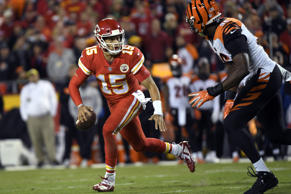 Kansas City Chiefs quarterback Patrick Mahomes (15) runs away from Cincinnati Bengals defensive end Carlos Dunlap (96) during the first half of an NFL football game in Kansas City, Mo., Sunday, Oct. 21, 2018. (AP Photo/Reed Hoffmann)