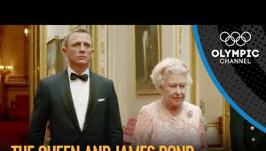 a man wearing a suit and tie: Daniel Craig reprises his role as British secret agent James Bond as he accompanies Her Majesty The Queen to the opening ceremony of the London 2012 Olympic Games.  The Ceremony also featured appearances from Mr. Bean, Monty Python and a re-imagining of the British Industrial Revolution.  Subscribe to the Olympic channel: http://bit.ly/1dn6AV5  Every two years, the world's finest athletes gather at the Olympic Games - a spectacular celebration of sporting excellence that captures the attention of billions of people around the world. However, the Games are about much more than just sport. They bring the Olympic values to life and provide a global arena for a unique combination of sport, culture, education and ceremonies.  At the Olympic Games in London 2012, about 10,500 athletes from 204 countries compete in 26 different sports, comprising 302 medal events. Whether athletes win a medal or not, they can forever call themselves Olympians. The sporting competitions are undoubtedly the central focus of the Olympic Games and participating in the Games is the ultimate goal for most athletes.  Every edition has its own story to tell and will be remembered for some truly remarkable performances from sporting legends such as Jesse Owens, Abebe Bikila, Jean-Claude Killy, Nadia Comaneci, Katarina Witt, Michael Phelps and Usain Bolt, to name just a few.  Find more about the Olympic Games at www.olympic.org/olympic-games