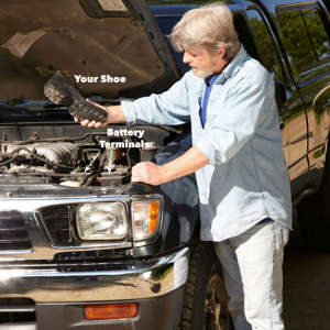 a man standing next to a car: car won't start shoe to battery terminal