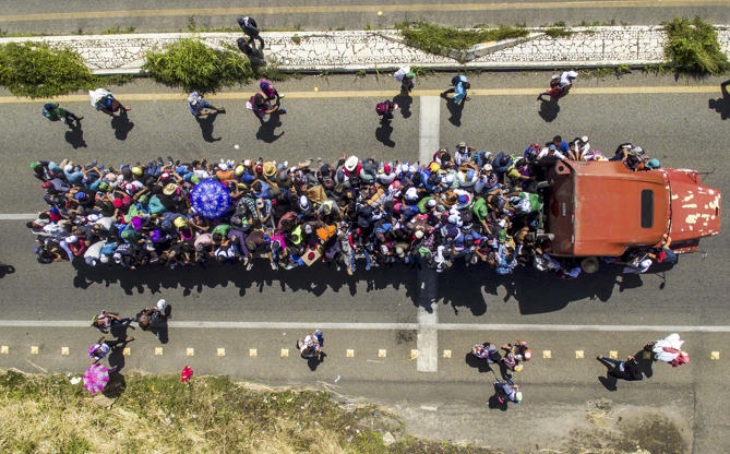 Slide 25 of 39: Aerial view of Honduran migrants onboard a truck as they take part in a caravan heading to the US, in the outskirts of Tapachula, on their way to Huixtla, Chiapas state, Mexico, on Oct. 22. - President Donald Trump on Monday called the migrant caravan heading toward the US-Mexico border a national emergency, saying he has alerted the US border patrol and military.