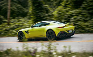 a person driving a car: The Aston's highlighter paint makes lane markers look drab by comparison. And its fluorescence distracts the eye from the Vantage's beauty.
