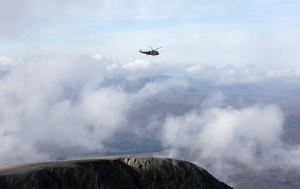 A Royal Navy rescue helicopter flies above Tower Ridge, at the summit of Britain's tallest mountain, Ben Nevis