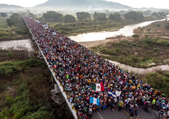 Slide 56 of 123: Aerial view of Honduran migrants heading in a caravan to the US, as the leave Arriaga on their way to San Pedro Tapanatepec, in southern Mexico on October 27, 2018. - Mexico on Friday announced it will offer Central American migrants medical care, education for their children and access to temporary jobs as long as they stay in two southern states. (Photo by Guillermo Arias / AFP)        (Photo credit should read GUILLERMO ARIAS/AFP/Getty Images)