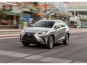 a car driving on a city street: 2019 Lexus NX Hybrid