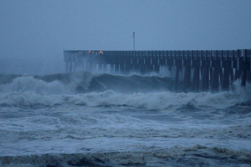 Slide 3 of 47: CAPTION: Waves crash along a pier as Hurricane Michael approaches Panama City Beach, Florida, U.S. October 10, 2018. REUTERS/Jonathan Bachman