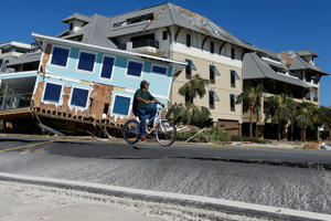 A man bikes past a house damaged by Hurricane Michael in Mexico Beach, Florida, U.S., October 12, 2018. REUTERS/Jonathan Bachman