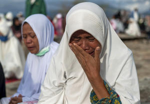A woman weeps during a prayer for the victims of Sept. 28 earthquake and tsunami on Talise Beach in Palu, Central Sulawesi, Indonesia, Friday, Oct. 12, 2018. A 7.5 magnitude earthquake rocked Central Sulawesi province on Sept. 28, triggering a tsunami and mudslides that killed a large number of people and displaced tens of thousands others. (AP Photo/Fauzy Chaniago)