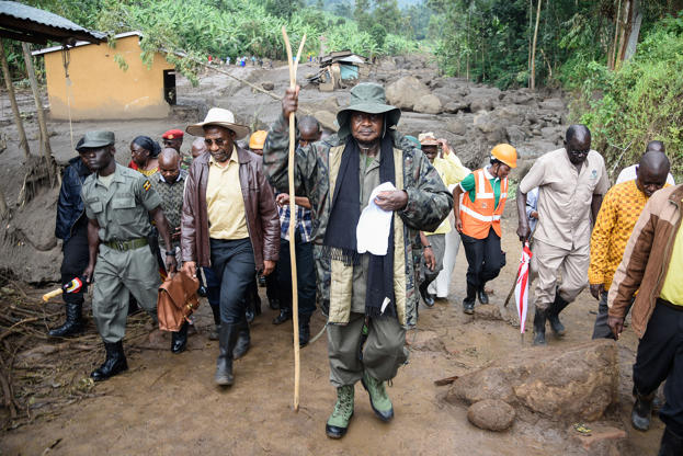 Slide 1 of 30: TOPSHOT - Ugandas President Yoweri Museveni (C) visits to the flood-ravaged village of Wanjenwa, eastern Uganda, on October 14, 2018. - At least 43 people were killed after a landslide caused by a river to burst its banks. (Photo by Isaac Kasamani / AFP) (Photo credit should read ISAAC KASAMANI/AFP/Getty Images)