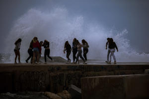 People run as a wave hits on a breakwater on the edge of the Mediterranean sea, ahead of a storm in Barcelona, Spain, Sunday, Oct. 14, 2018. A weakened hurricane Leslie slammed into the coast of Portugal, leaving 27 people injured as it uprooted trees, brought down power lines and smashed store windows with gusting winds and heavy rain. Leslie moved east Sunday across the Iberian Peninsula to Spain, where authorities issued warnings for heavy rains and storm conditions for the northern part of the country.