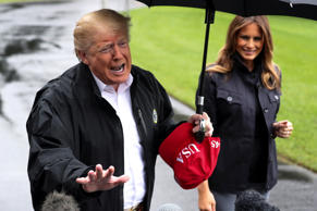 U.S. President Donald Trump talks to reporters as he departs with first lady Melania Trump to tour hurricane damage in Florida from the White House in Washington, U.S., October 15, 2018.