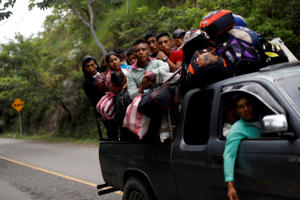 Honduran migrants, part of a caravan trying to reach the U.S., are pictured inside a pick up in Quezaltepeque, Guatemala October 16, 2018.