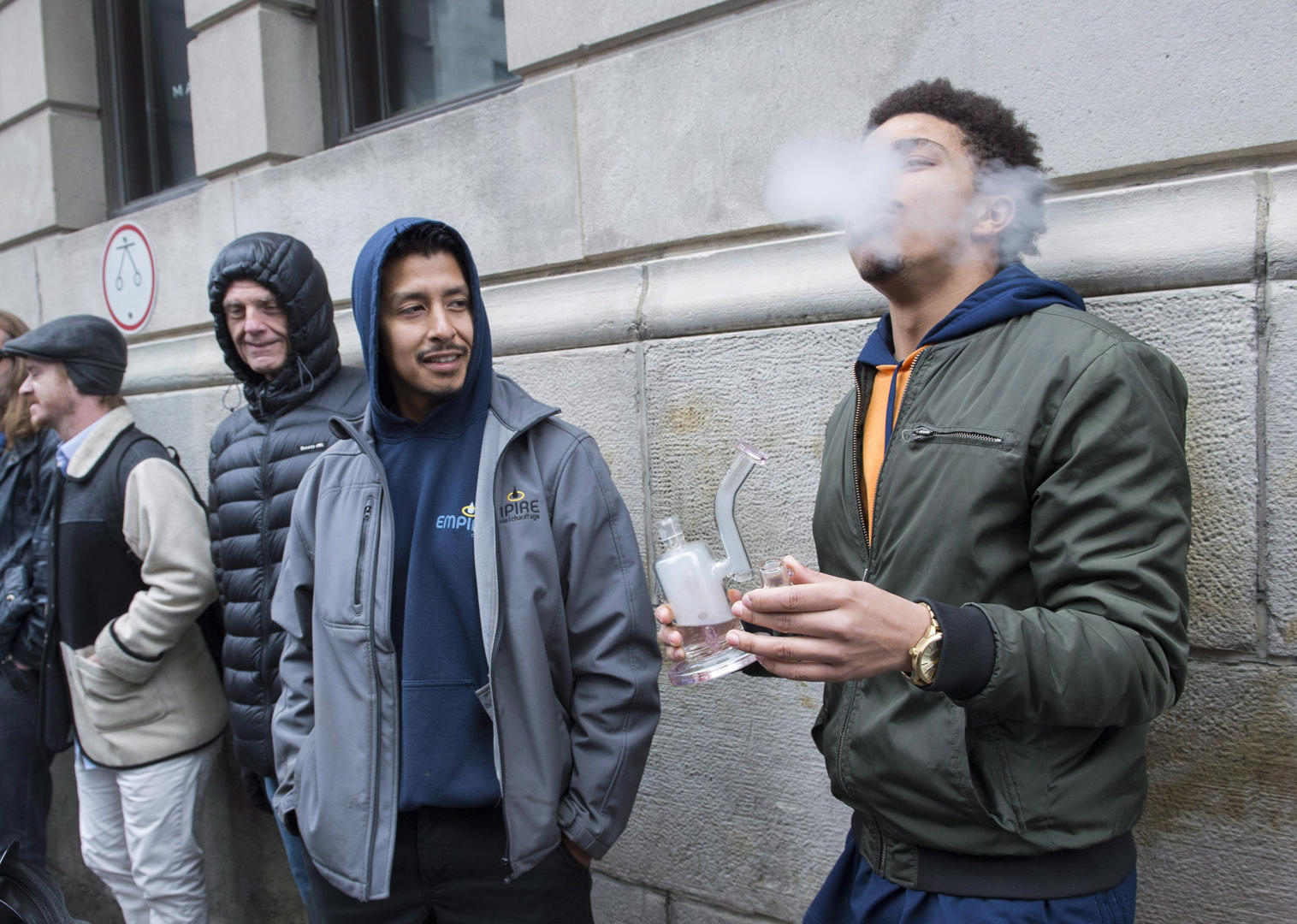 Slide 18 of 31: A man smokes from a bong as he waits in line to purchase legal cannabis outside a government cannabis store in Montreal, Wednesday, October 17, 2018.