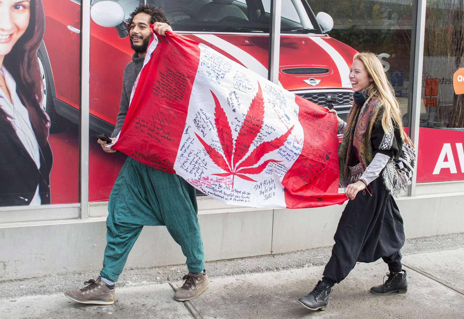 Slide 10 of 31: People hold up a Canadian flag with a marijuana logo on it outside a government cannabis store in Montreal, Wednesday, October 17, 2018.