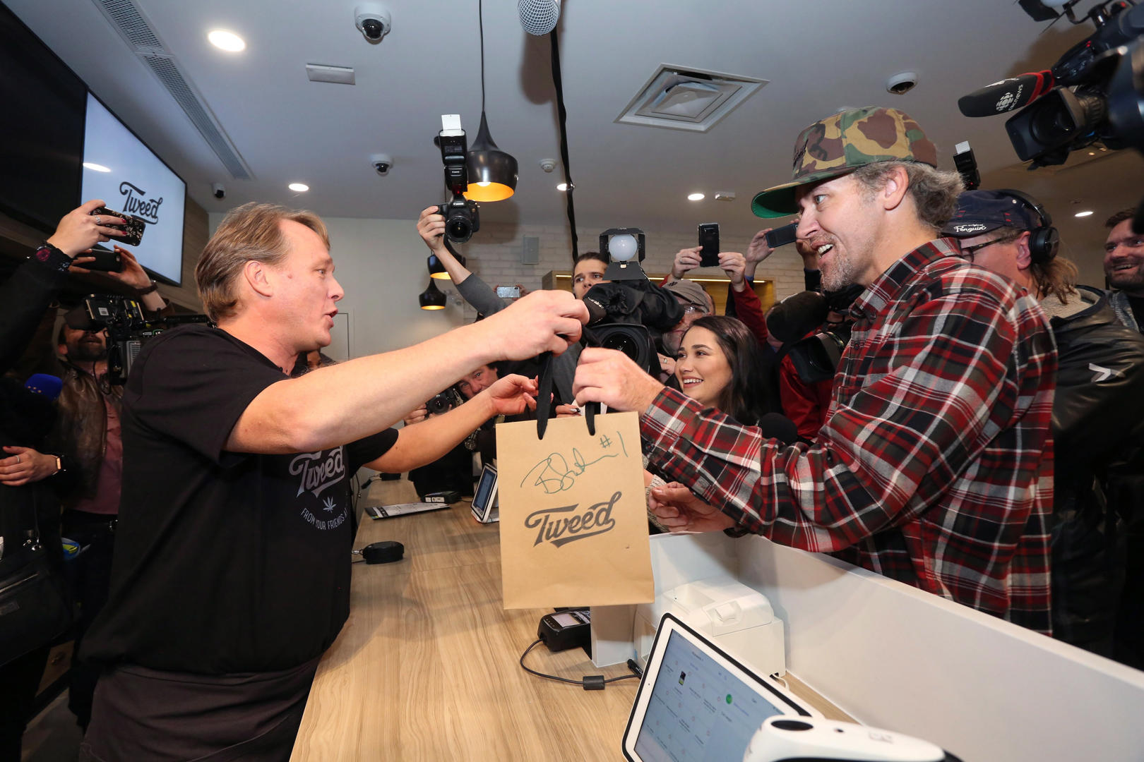 Slide 8 of 31: Canopy Growth CEO Bruce Linton, left to right, passes a bag with the first legal cannabis for recreation use sold in Canada to Nikki Rose and Ian Power at the Tweed shop on Water Street in St. John's N.L. at 12:01 am NDT on Wednesday October 17, 2018.