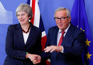 Prime Minister Theresa May is welcomed by European Commission President Jean-Claude Juncker ahead of the European Union leaders summit in Brussels