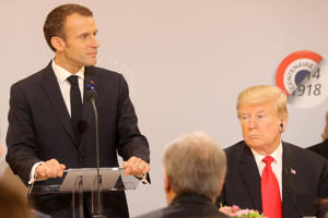French President Emmanuel Macron delivers a speech as U.S. President Donald Trump looks on, before a lunch at the Elysee Palace, during commemorations for Armistice Day, 100 years after the end of World War One, in Paris, France, November 11, 2018. Jacques Demarthon/Pool via REUTERS
