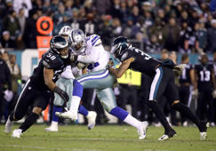 Dallas Cowboys running back Ezekiel Elliott, center, runs with the ball as Philadelphia Eagles middle linebacker Jordan Hicks (58) and defensive back Tre Sullivan try to stop him during the second half of an NFL football game, Sunday, Nov. 11, 2018, in Philadelphia. (AP Photo/Matt Rourke)