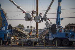 Pacific Gas and Electric Company crews work to restore power near fire-damaged Cardinal Newman High School on October 14, 2017 in Santa Rosa, California.