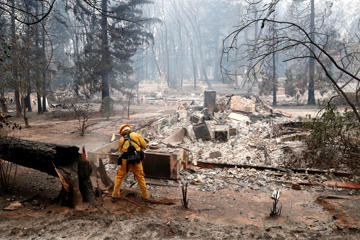 A firefighter extinguishes a hot spot in a neighbourhood destroyed by the Camp Fire in Paradise, California, November 13.