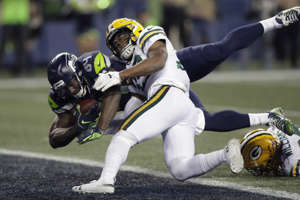 Seattle Seahawks tight end Ed Dickson, left, dives past Green Bay Packers defensive back Ibraheim Campbell, center, to score a touchdown after a reception during the second half of an NFL football game, Thursday, Nov. 15, 2018, in Seattle. (AP Photo/Stephen Brashear)