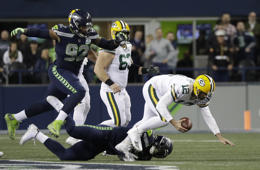 Green Bay Packers quarterback Aaron Rodgers (12) is tripped up by Seattle Seahawks defensive end Frank Clark, center, as Seahawks defensive tackle Nazair Jones, left, leaps in during the second half of an NFL football game, Thursday, Nov. 15, 2018, in Seattle. (AP Photo/Elaine Thompson)