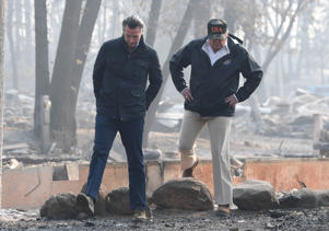 US President Donald Trump walks with Lieutenant Governor of California, Gavin Newsom, as they view damage from wildfires in Paradise, California on November 17, 2018. - President Donald Trump arrived in California to meet with officials, victims and the 'unbelievably brave' firefighters there, as more than 1,000 people remain listed as missing in the worst-ever wildfire to hit the US state. (Photo by SAUL LOEB / AFP)        (Photo credit should read SAUL LOEB/AFP/Getty Images)