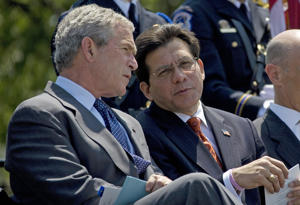 Then-President George W. Bush speaks with Attorney General Alberto Gonzales at the U.S. Capitol in 2007.