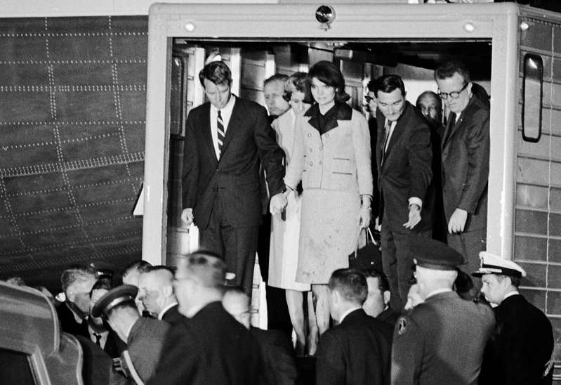 The coffin of President John Fitzgerald Kennedy is moved from Air Force One to an ambulance upon arrival at Andrews Air Force Base. Robert Kennedy, Jacqueline Kennedy, Kenny O'Donnell, and Larry O'Brien stand side-by-side in the doorway. Photo by Wally McNamee/ The Washington Post via Getty Images