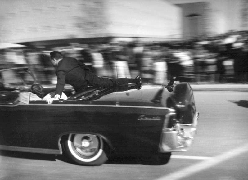 FILE - In this Nov. 22, 1963 file photo, the limousine carrying mortally wounded President John F. Kennedy races toward the hospital seconds after he was shot in Dallas. Secret Service agent Clinton Hill is riding on the back of the car,  (AP Photo/Justin Newman, File)