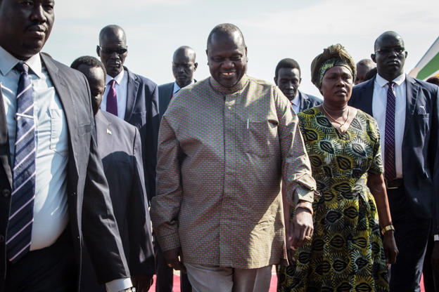 Diapositive 2 sur 31: Le chef des rebelles du Sud-Soudan, Riek Machar (C), arrive à l'aéroport international de Juba avec son épouse pour assister à une cérémonie de la paix à Juba, au Soudan du Sud, le 31 octobre 2018. - Le chef des rebelles du Sud-Soudan, Riek Machar, est rentré dans la capitale. Juba pour la première fois en plus de deux ans à participer à une cérémonie de paix.  (Photo de Akuot CHOL / AFP) (Le crédit photo devrait correspondre à AKUOT CHOL / AFP / Getty Images)