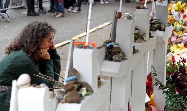Slide 1 of 89: Anat Halevy Hochberg, of Brooklyn, NY., visits a makeshift memorial outside the Tree of Life synagogue where 11 people were killed on Oct. 27 while worshipping, in the Squirrel Hill neighborhood of Pittsburgh, Thursday, Nov. 1, 2018. (AP Photo/Gene J. Puskar)