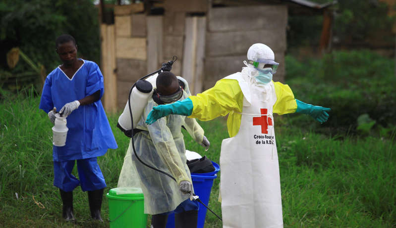 In this photo taken Sunday, Sept 9, 2018, a health worker sprays disinfectant on his colleague after working at an Ebola treatment centre in Beni, Eastern Congo. The current Ebola outbreak in northeastern Congo has become a testing ground with one aid group for the first time treating confirmed Ebola victims in individual biosecure units used in emergencies involving highly infectious diseases. (AP Photo/Al-hadji Kudra Maliro)