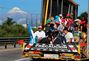 Central American migrants begin their morning trek with a free ride on a truck, with Pico de Orizaba volcano in the background, as part of a thousands-strong caravan hoping to reach the U.S. border as they leave Cordoba, Veracruz state, Mexico, Monday, Nov. 5, 2018.