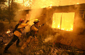 PARADISE, CA - NOVEMBER 09:  Firefighters try to keep flames from burning home from spreading to a neighboring apartment complex as they battle the Camp Fire on November 9, 2018 in Paradise, California. Fueled by high winds and low humidity, the rapidly spreading Camp Fire ripped through the town of Paradise and has quickly charred 70,000 acres and has destroyed numerous homes and businesses in a matter of hours. The fire is currently at five percent containment.  (Photo by Justin Sullivan/Getty Images)