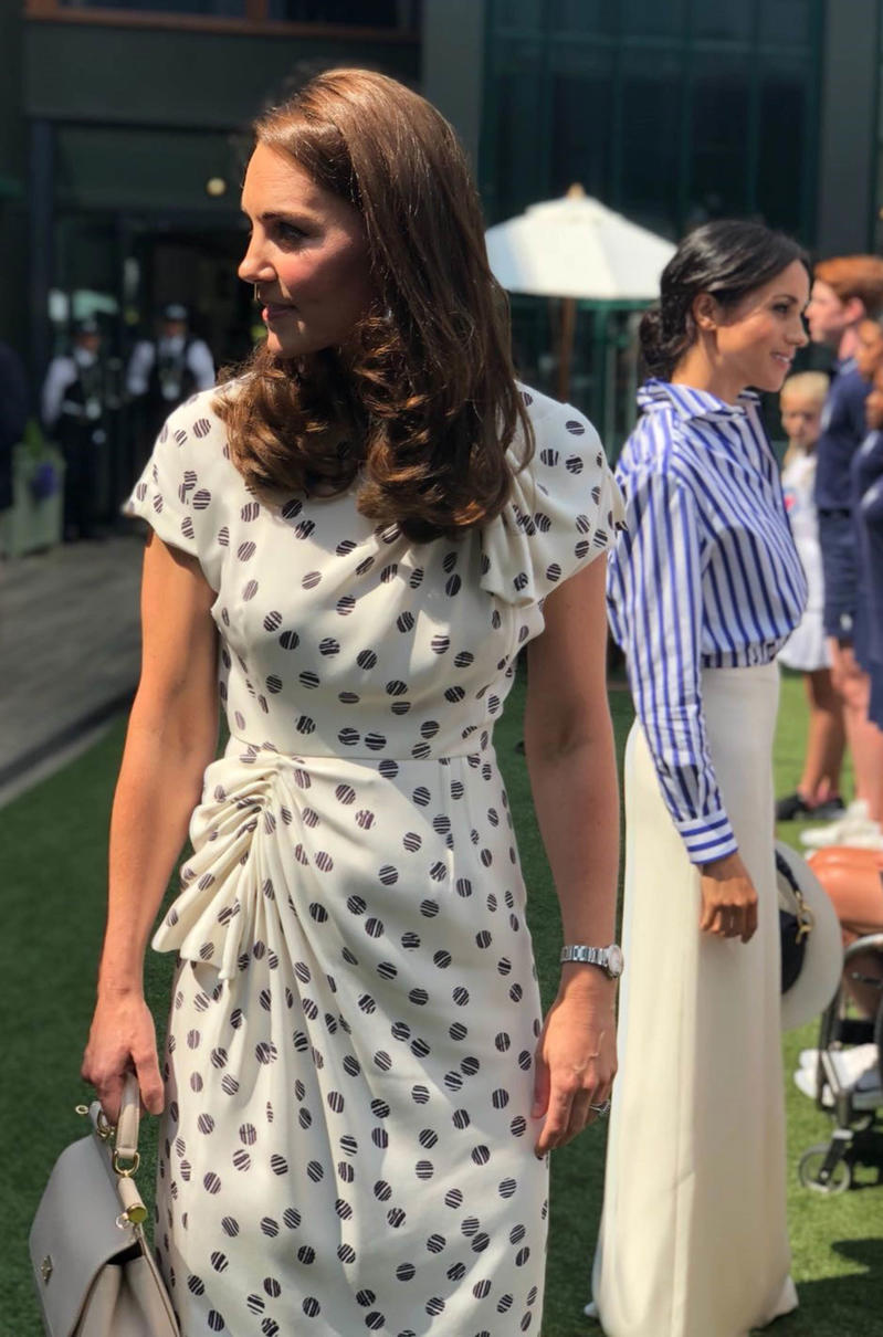 The Duchess of Cambridge (left) and the Duchess of Sussex meet young people during a visit to the Wimbledon Championships at the All England Lawn Tennis and Croquet Club, Wimbledon.
