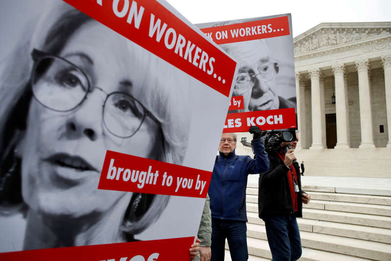 Mike Lohman, center, with the American Federation of Teachers, rallies among signs depicting Education Secretary Betsy DeVos and Koch Brother, Charles Koch, as he and others protest in support of unions outside of the Supreme Court, Monday, Feb. 26, 2018, in Washington. The Supreme Court takes up a challenge in a case that could deal a painful financial blow to organized labor. The court is considering a challenge to an Illinois law that allows unions representing government employees to collect fees from workers who choose not to join.(AP Photo/Jacquelyn Martin)