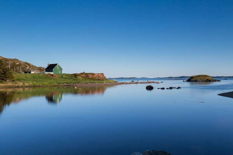 A green house reflected in a calm lake, Newfoundland, Canada.
