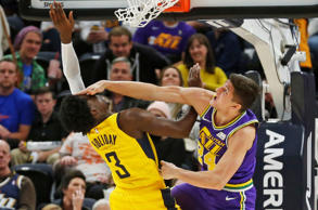 Utah Jazz guard Grayson Allen, right, battles under the basket with Indiana Pacers guard Aaron Holiday (3) in the second half during an NBA basketball game Monday Nov. 26, 2018, in Salt Lake City. (AP Photo/Rick Bowmer)