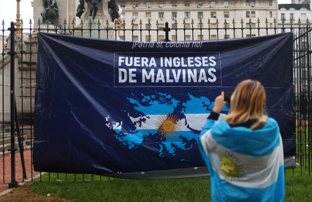 """Diapositiva 41 de 55: A woman takes a picture of a banner depicting the Falkland Islands in the Argentinian colors during a protest ahead of the G20 leaders summit, in Buenos Aires, Argentina November 29, 2018. The banner reads """"The English out of the Falkland Islands"""". REUTERS/Pilar Olivares"""