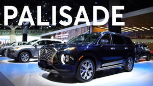 a car parked in front of a sign: 2018 LA Auto Show: 2020 Hyundai Palisade