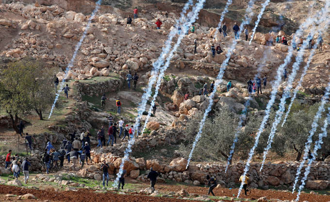 Slide 4 of 36: Tear gas canisters are fired by Israeli troops towards Palestinians during a protest against Israeli land seizures for Jewish settlements, near Ramallah in the occupied West Bank November 30, 2018.
