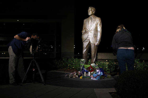 Slide 1 of 14: Members of the media film a makeshift memorial at the foot of a statue outside the George H.W. Bush Presidential Library and Museum, a day after the 41st president of the United States died, in College Station, Texas, U.S., December 1, 2018. REUTERS/Loren Elliott - RC17D5ABE7C0
