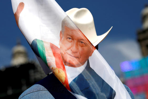 Slide 9 of 36: Andres Manuel Lopez Obrador holds a banner while waiting for his arrival at Zocalo square in Mexico City, Mexico December 1, 2018.