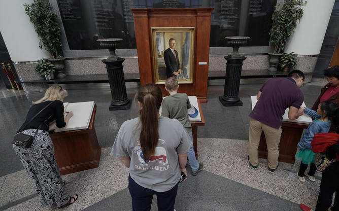 Slide 2 of 14: Visitors to the George H.W. Bush Presidential Library and Museum sign condolence books Saturday, Dec. 1, 2018, in College Station.  Bush died at his home Friday night. He was 94. (AP Photo/David J. Phillip)