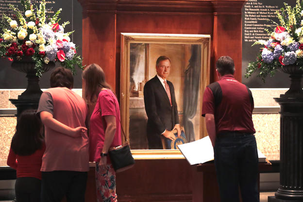Slide 5 of 36: Visitors sign a guest book at the George H.W. Bush Presidential Library Center on December 1, 2018 in College Station, Texas. Bush, who died on November 30, will be buried next to his wife Barbara at the library on Thursday.  (Photo by Scott Olson/Getty Images)