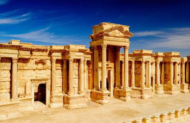 """Slide 26 de 26: Antes do início da Guerra Civil da Síria, em 2011, o país tinha uma vibrante indústria de turismo, girando especialmente ao redor dos mercados das cidades, além dos templos religiosos, teatros e palácios que foram construídos no Império Romano, especialmente a antiga cidade de Palmira (foto). O anfiteatro da cidade e outros marcos históricos foram parcialmente destruídos pelo Estado Islâmico, em 2017. Outrora vibrantes, as cidades antigas de Aleppo e Homs também foram amplamente destruídas. """"O Estado Islâmico e a guerra destruíram o passado e o presente"""", observou um ex-guia turístico, em um artigo para o Independent. Desde novembro de 2011, Estados Unidos, Canadá e Reino Unido recomendam que seus cidadãos saiam da Síria e se mantenham longe do país por causa do interminável conflito."""